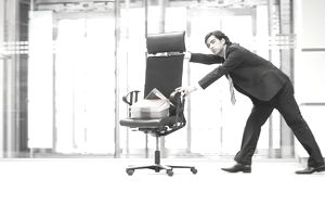 Businessman pushing office chair with supplies