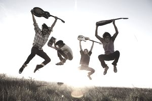 Men jumping with musical instruments