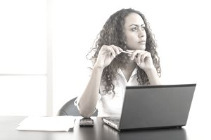 USA, New Jersey, Jersey City, Office worker sitting by desk with laptop