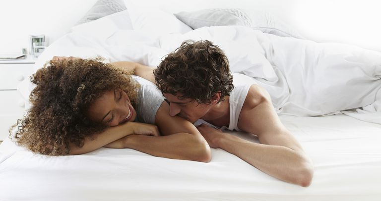 Couple in bed being affectionate, they know the best time to get pregnant is before ovulation