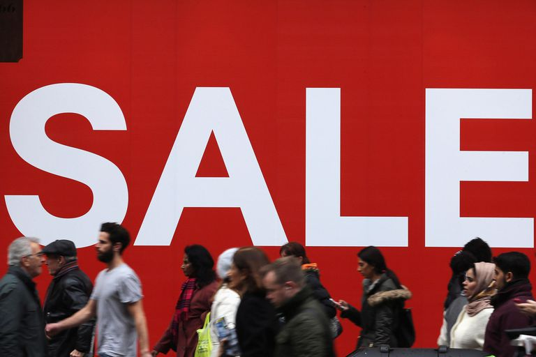 Shoppers make their way past a sale sign outside a clothing store on Oxford Street on December 24, 2012 in London, England.
