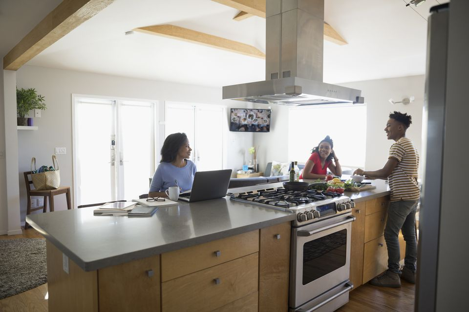 African American mother working at laptop and teenage children cooking in kitchen