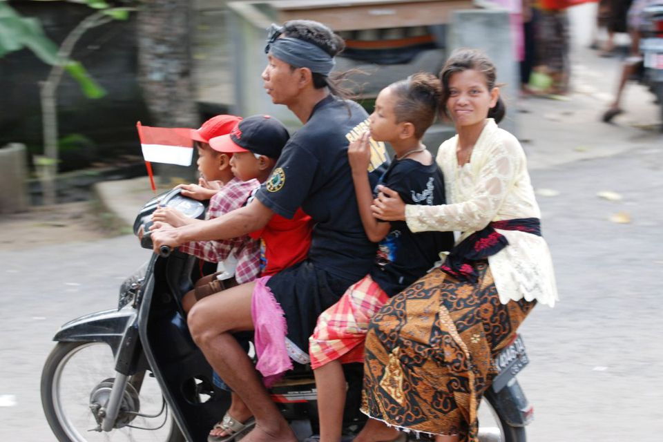 Family riding one motorbike in Bali, Indonesia