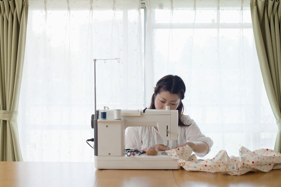 The woman using a sewing machine.