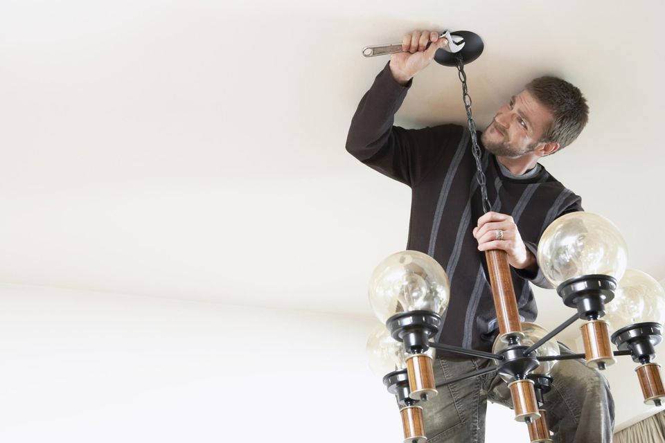Man using wrench to hang lighting fixture from ceiling