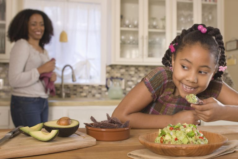 A child eating chips with guacamole.