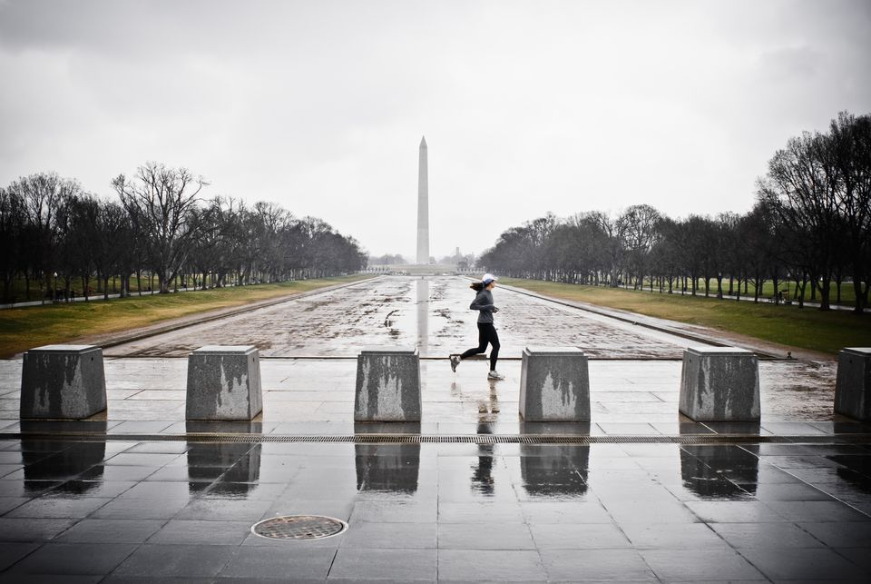 A female runner by the empty reflecting pool by the Lincoln Memorial.