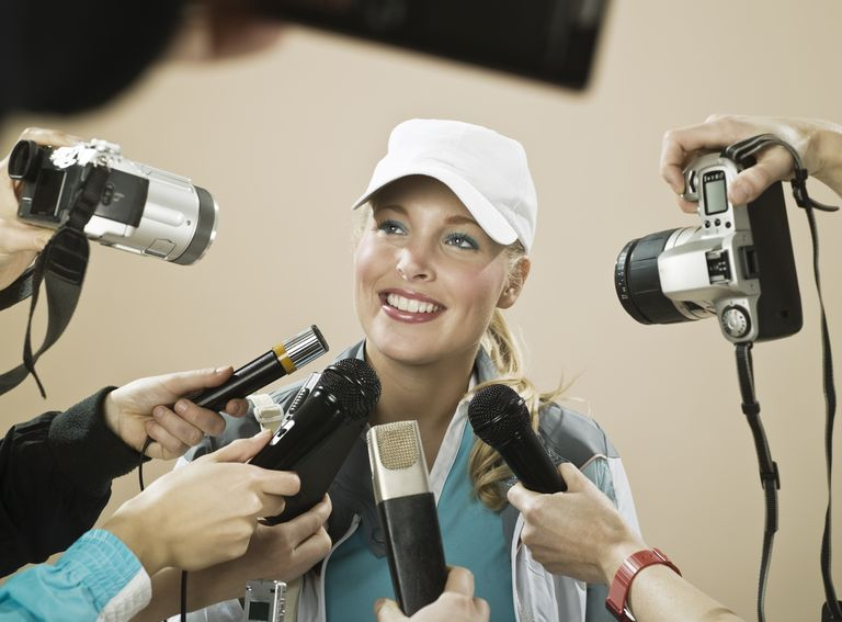 Female athlete smiling at press conference, studio shot