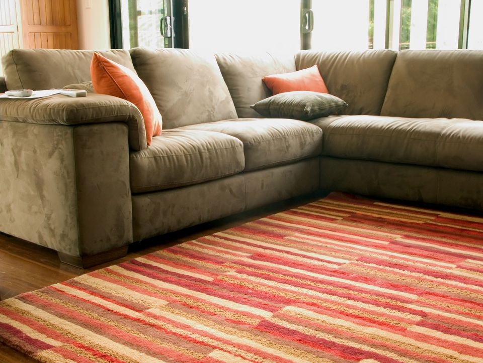 Striped area rug over hardwood in living room.