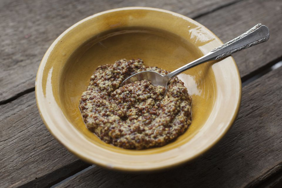 Bowl of mustard on wooden table