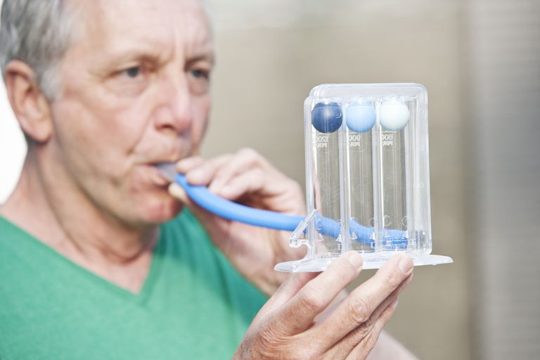 Male person performing lung function test by using a triflow