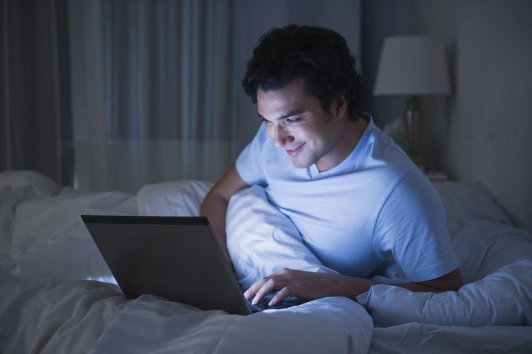 USA, New Jersey, Jersey City, Man using laptop in bed