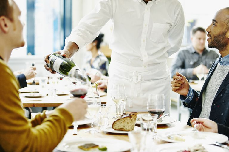 waiter pouring wine for men at restaurant