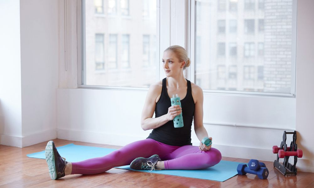 Model holding water bottle in fitness studio