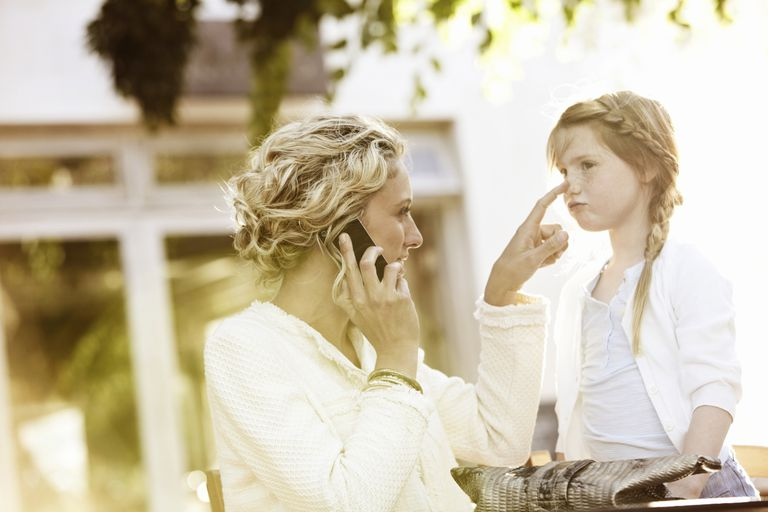 Mother having phone call nudging daughter in sun