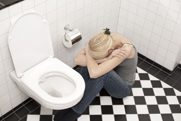 Despaired anorexic young woman at the toilet