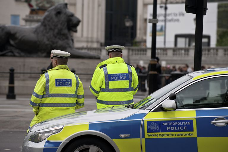 Metropolitan police officers and car on duty in central London.