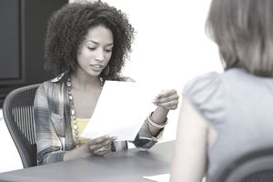 African American woman reading a resume while taking interview of a Caucasian woman