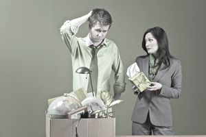 Man in green shirt with office things in box is offered kleenix by a woman