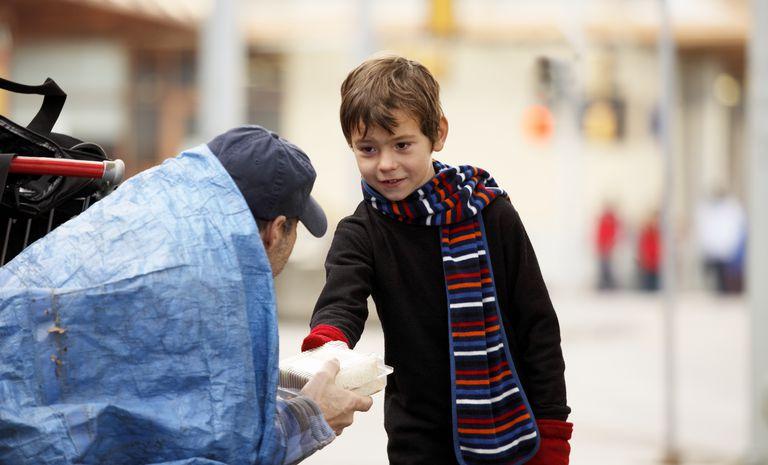Child giving homeless man food