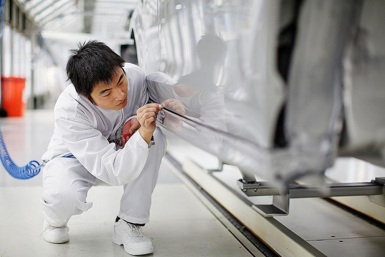 A Chinese man works on a car production line. China is now an industrial society.