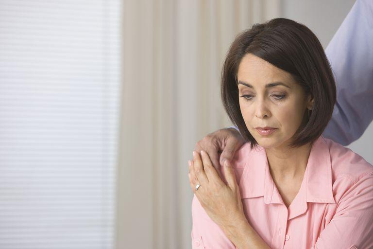 Sad Hispanic woman being comforted by husband