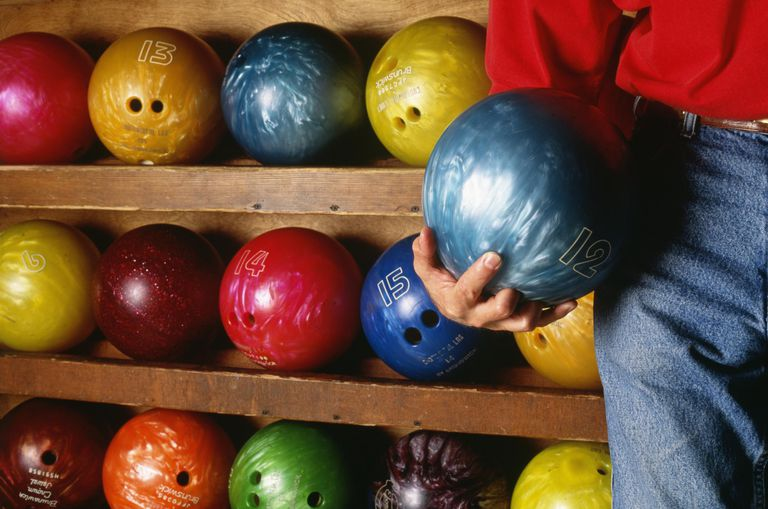 This man selected a bowling ball from the rack of house balls.