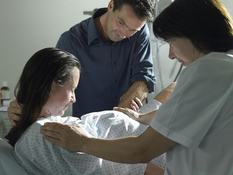 Midwife and husband supporting pregnant woman, giving birth in hospital