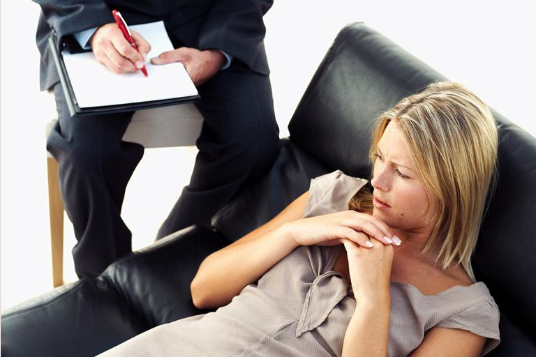 woman lying on sofa and man sitting besides her on chair writing