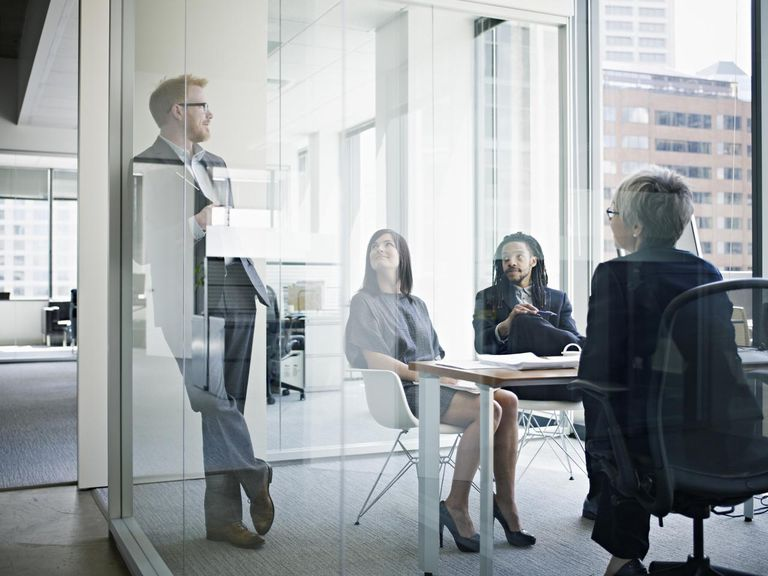 Four coworkers in discussion in office