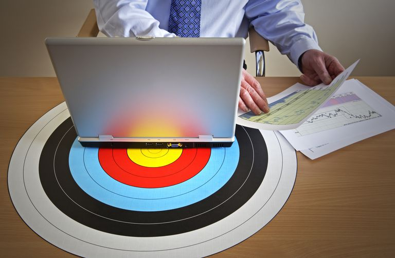 Businessman at desk with laptop on target holding charts, mid section