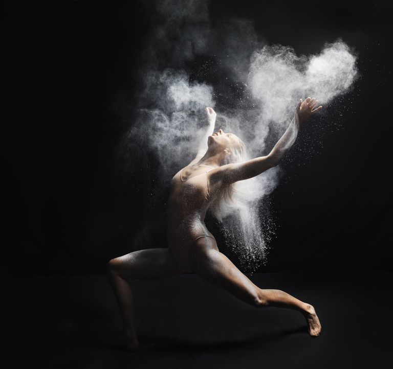 Young dancer performing with white powder