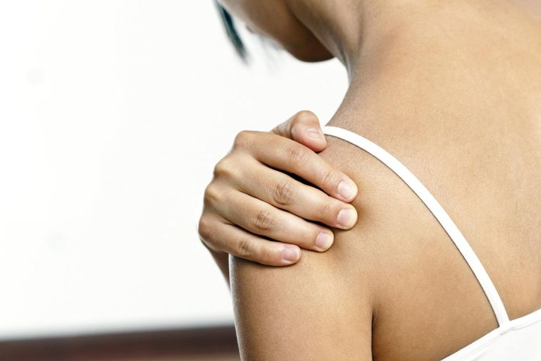 Young woman feeling pain in her shoulder