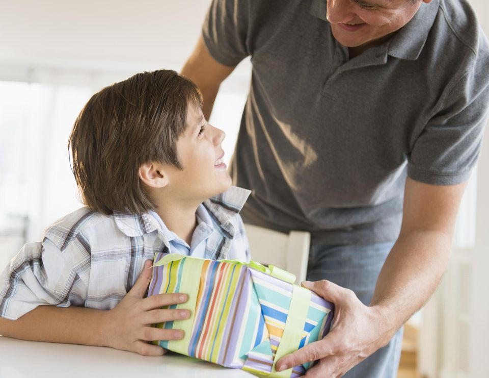 Boy (8-9) giving gift to father