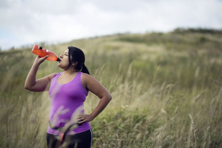 overweight woman exercising and drinking water