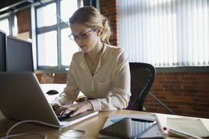 a businesswoman working at laptop at office desk