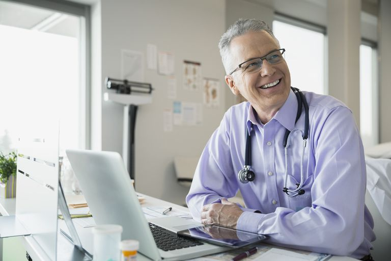 Smiling doctor at laptop in clinic office