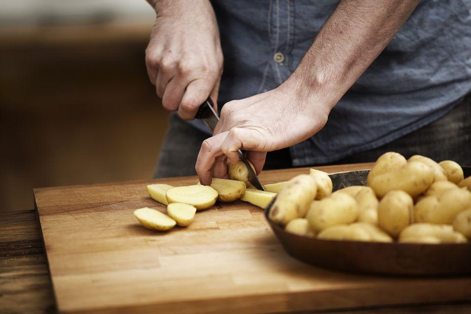 Man cutting potatoes in kitchen