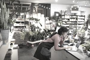 Female shop owner talking on cell phone working at laptop at plant shop counter