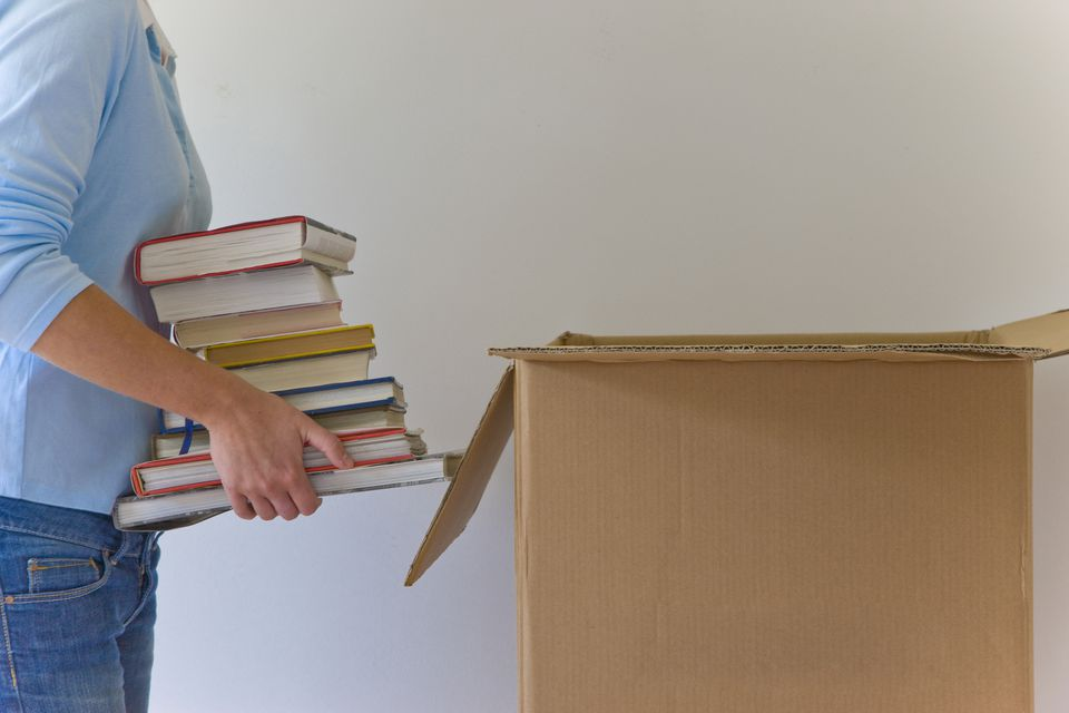 Woman standing next to cardboard box holding a pile of books