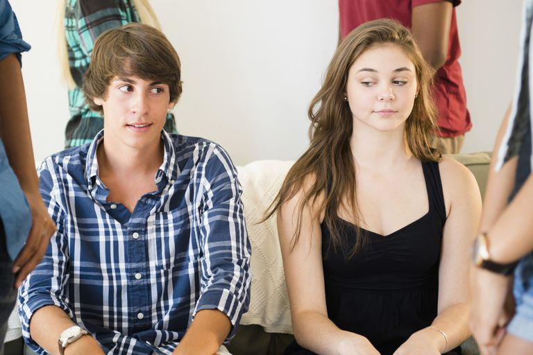 Teen boy and girl looking awkwardly at each other