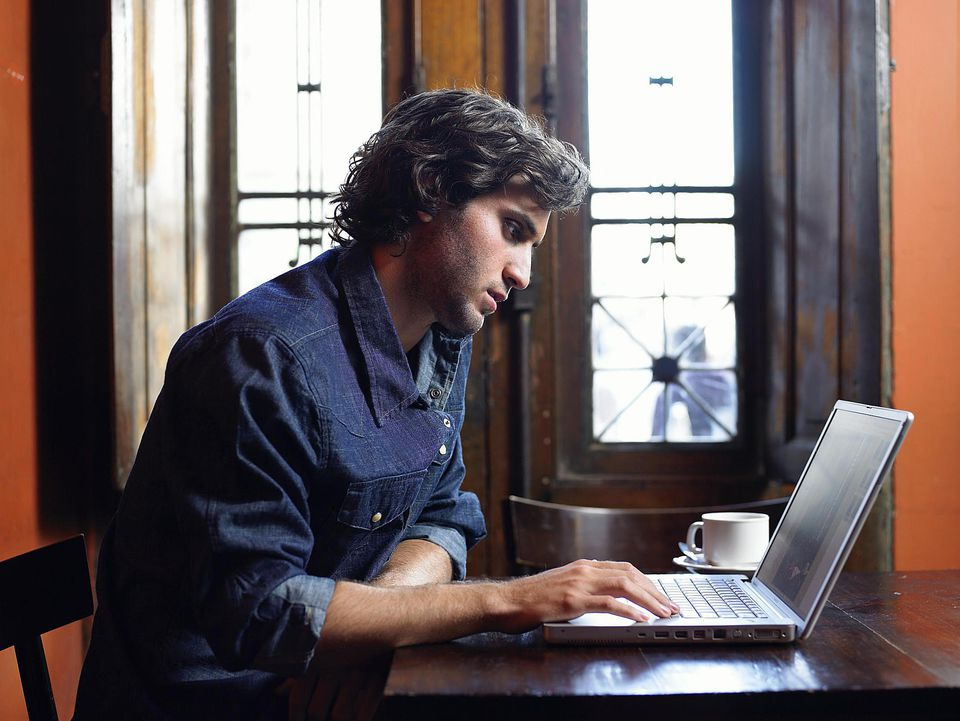 Young man working on laptop computer in cafe