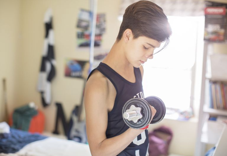 Teenage boy exercising with dumb bell