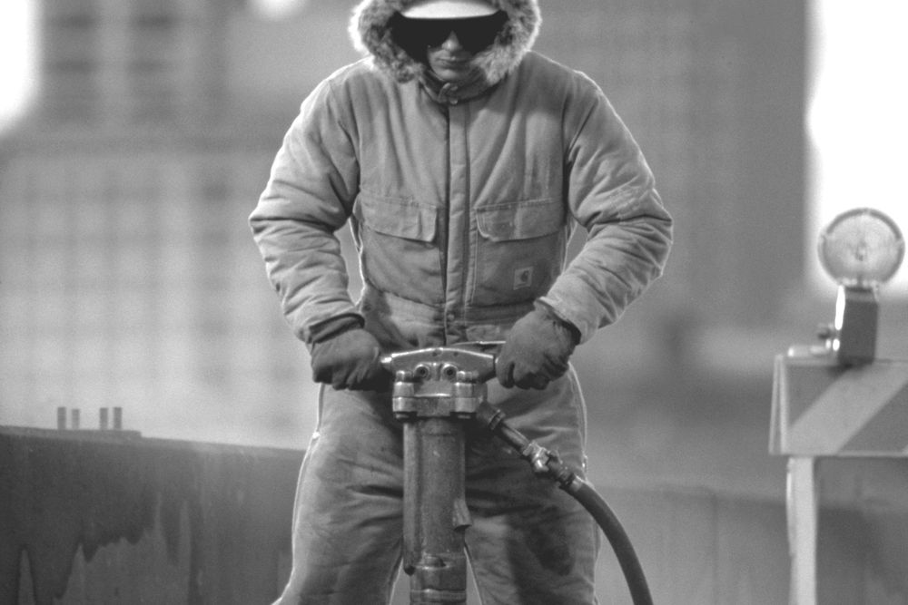 Workman using pneumatic drill in winter, Seattle, Washington, USA
