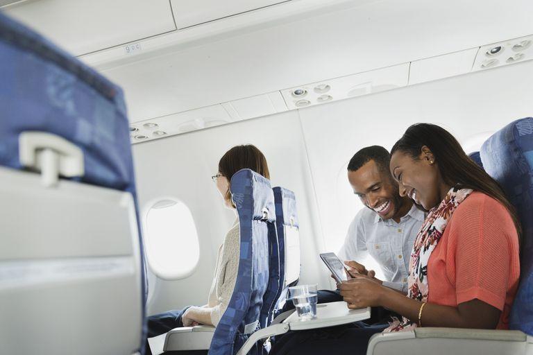 A couple uses an iPad on a plane.