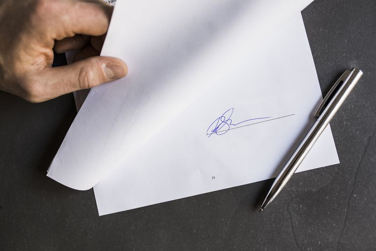 Cropped image of businessman holding document with signature