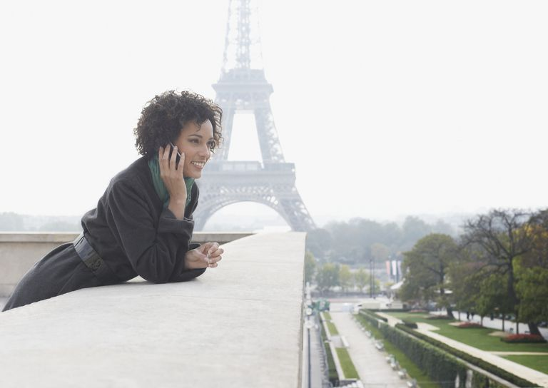 Woman outdoors on her mobile phone by the Eiffel Tower