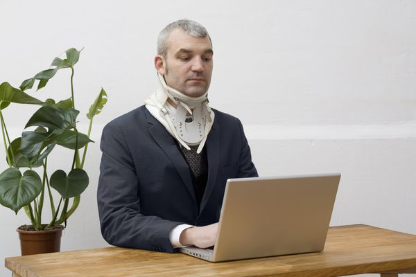 Computer worker wearing a neck brace
