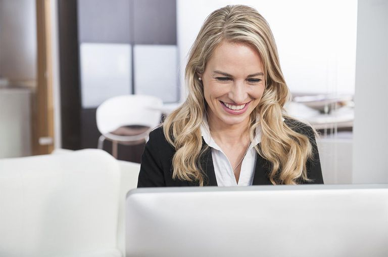 Mid adult businesswoman working in office on personal computer