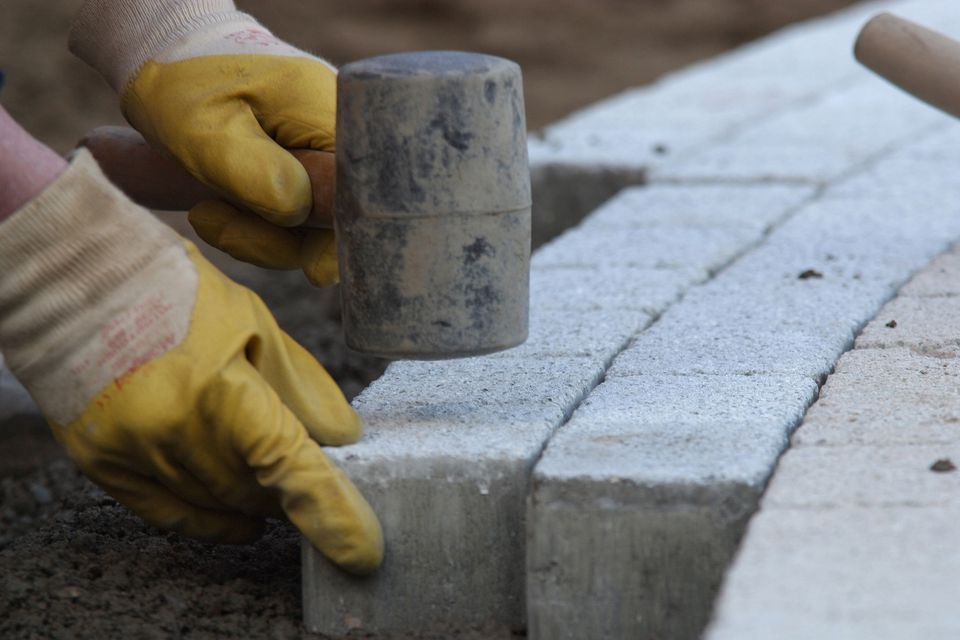 Image: tapping pavers into place with a rubber mallet.